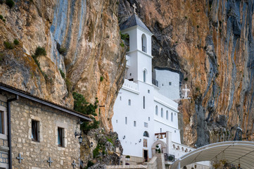 Ostrog monastery upper church. White tower in the cave of a mountain. Montenegro sightseeing.