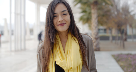 Single joyful grinning woman in yellow scarf standing outdoors need palm trees and buildings