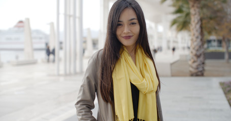 Stylish young woman on a waterfront promenade standing looking at the camera with a friendly smile  upper body