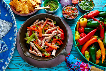 chicken fajitas in a pan chili and sides Mexican