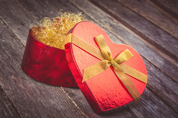 Valentines Day composition - red heart with ribbon bow on wooden background. Instagram color toning