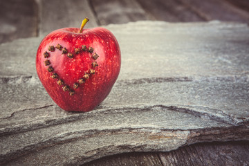 Valentines Day card - red apple with heart on stone background. Instagram colored toning