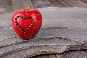 Valentines Day card - red apple with heart on stone background
