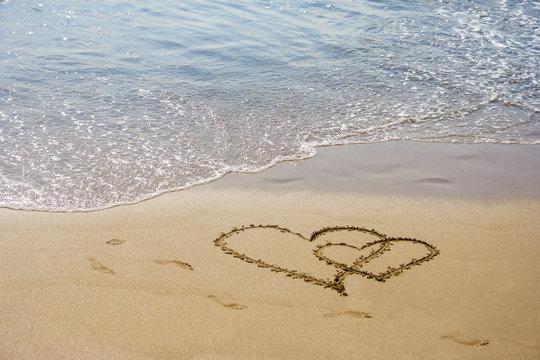 Sand hearts couple at the beach