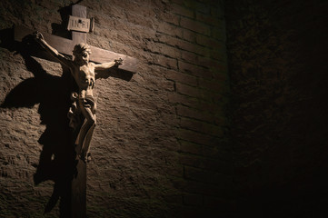 Dark artistic cross on a shaded rough textured brick wall