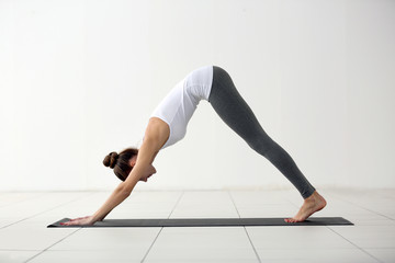 Health concept. Young attractive woman does yoga exercise in the gym  against white wall