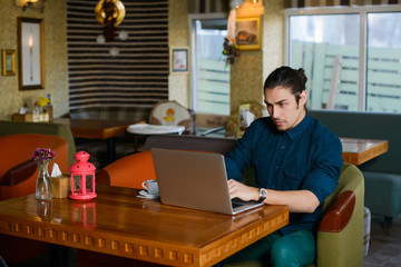 Young man drinking coffee and working on laptop in a cafe