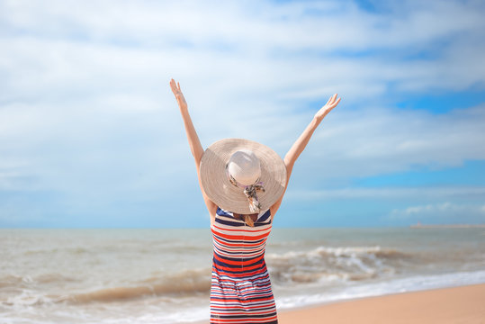 Back view of romantic lady enjoying summer beach and sun, waving at sea. Concept of feeling and freedom