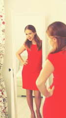woman in a red dress looks in the mirror