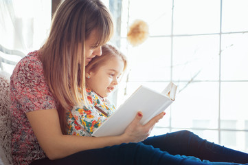 Portrait of a smiling young cute mother and daughter reading a book lying and relax on the bed in a bright big white room