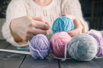 Female hands with purple manicure are knitted metal spokes of a