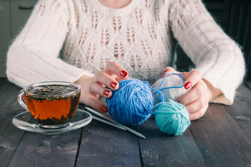 Woman hands with cup of tea and wool yarn balls on a wooden tabl
