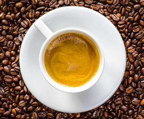 Cup of Coffee on and with Coffee Beans