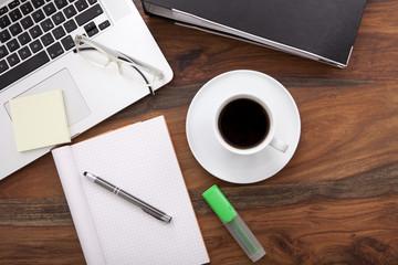 Arbeistplatz mit Laptop, Kaffee, leerem Block und Ordner,