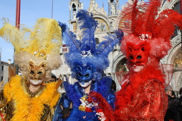italy, carnival masks in venice posing in san marco square. Three colored cats, red yellow and blue