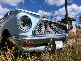 Grill of abandoned blue car in the tall grass - landscape photo
