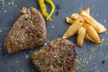 Grilled T-bone steak seasoned with spices and fresh herbs served