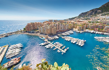 Monaco, Fontvieille, 29.08.2015: Port Fontvieille, panorama, topview from Monaco Ville, azur water, sun reflections on the water, harbor, sunny day, luxury apartments, yachts, rocks