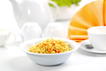 Stewed rice with a carrot in a white bowl on a table