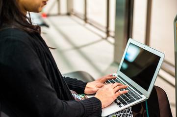 待ち時間にノートパソコンを使う女性