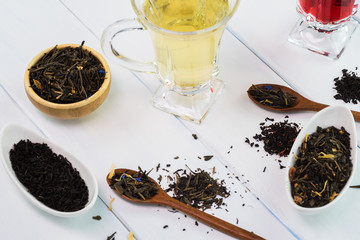 Assortment of dry tea and glass cup with green tea and red tea.