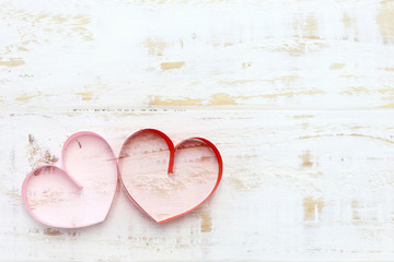 red and pink paper heart on white wood background