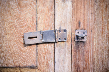 Close up of old door bolt on wooden background