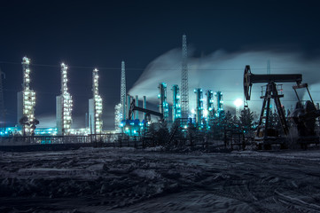 Oil rigs and brightly lit industrial site at night.