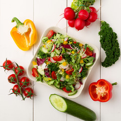 Spring salad with fresh vegetables from radishes and kale