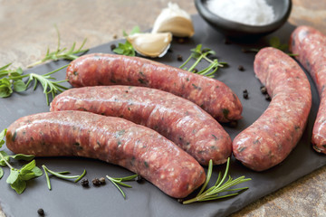 Raw Sausages on Slate with Herbs and  Spices