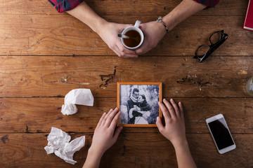 Sad mans, womans hands holding broken picture of romantic couple.