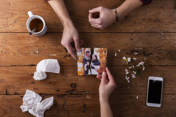 Sad mans, womans hands holding torn picture of romantic couple.