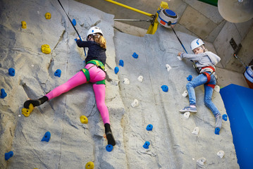 Two athlete girls climbing on blue wall