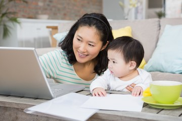 Happy mother with baby daughter using laptop