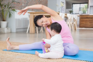 Happy mother doing yoga on mat while looking at baby daughter