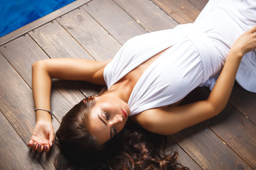 Charming young woman lying on brown wooden floor in white long dress. summer style