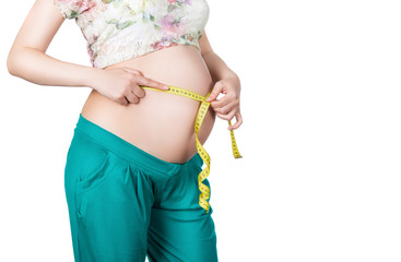 Pregnant woman measuring her waist and stomach.