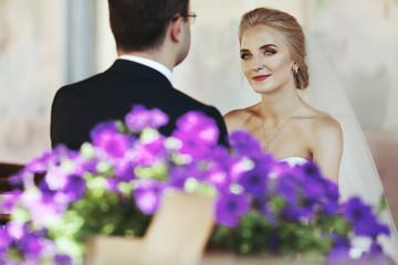 Emotional blonde bride holding hands with handsome groom, flower