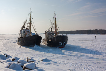 two old trawlers frozen in the ice