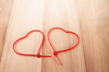 Cable ties heart shape on wood background , holiday abstract bac