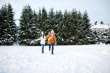 happy couple running in winter snow