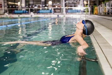 Attractive woman with cap and goggles in the pool