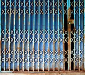 Old rusty blue folding metal door