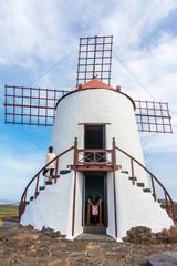 Young woman standing in a traditional Spanish windmill in Lanzarote, Canary Islands, Spain