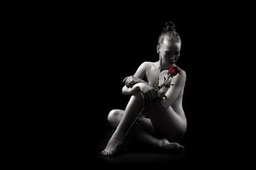 klassieke naakte jonge sexy meid met rode roos zit op de vloer op zwarte achtergrond