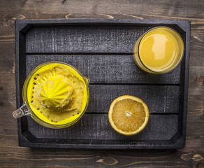 juicer and a glass of juice with sliced oranges in a wooden tray on wooden rustic background top view close up