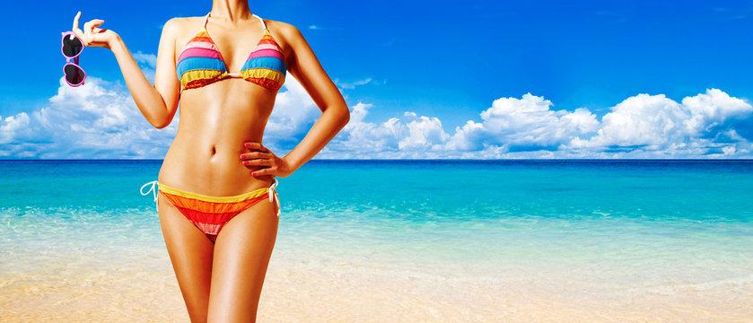 Beautiful woman body with colorful bikini. Holding sunglasses on the beach. Perfect shining skin.