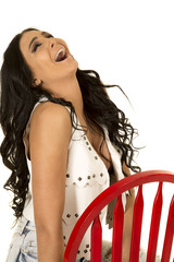 woman in white vest and black bra red chair head back laughing