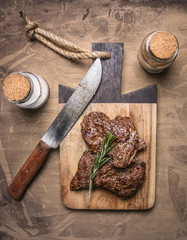 appetizing beef, grilled, on a cutting board with rosemary, spices and knife for meat on wooden rustic background top view close up