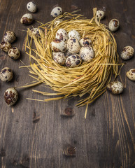 Fresh quail eggs laid in the nest and around on the wooden table on wooden rustic background top view close up